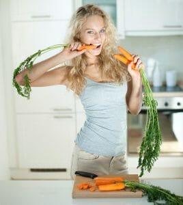 une femme mange des carottes