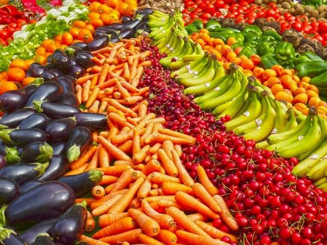 stand avec carottes, bananes, cerises, poivrons, aubergines