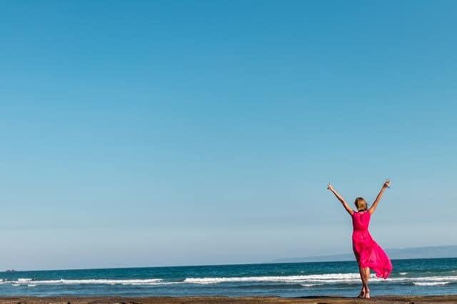une femme en robe rouge debout sur la côte