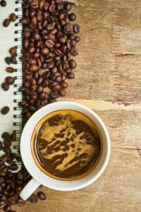 les grains de café et le café dans une tasse