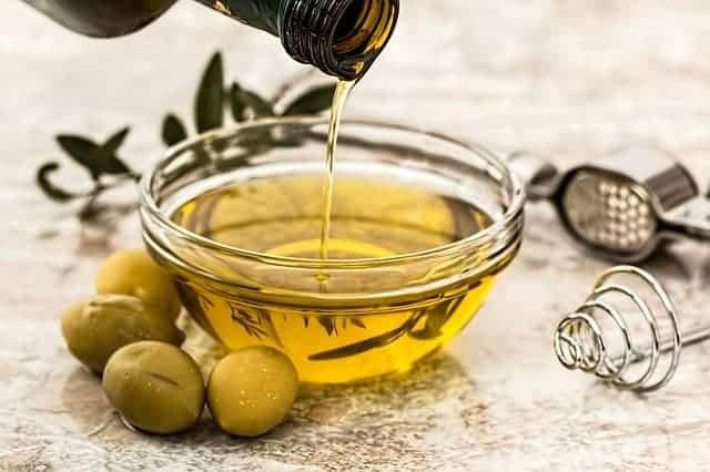 huile versée dans un bol, olives vertes à côté