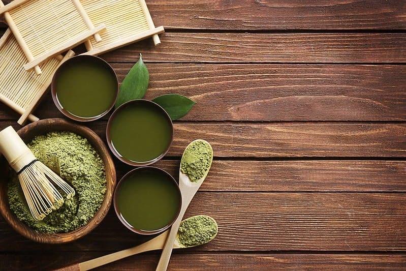 hé vert matcha en poudre dans une salade et des tasses de liquide