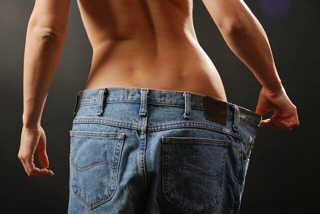 une femme mince avec un pantalon trop grand