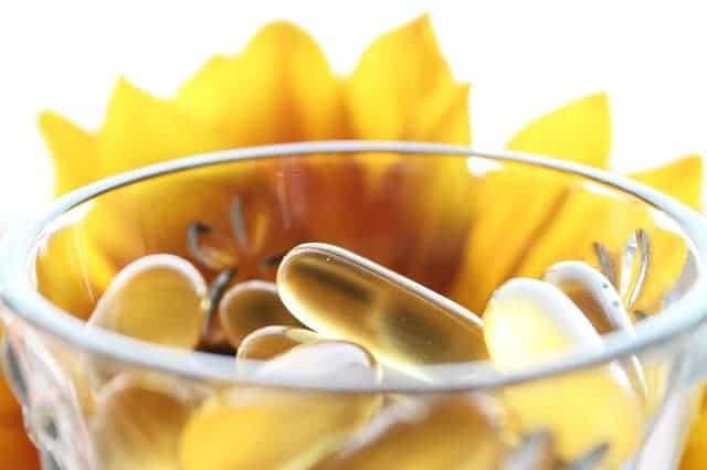 des comprimés dans un verre, avec une fleur jaune en arrière-plan