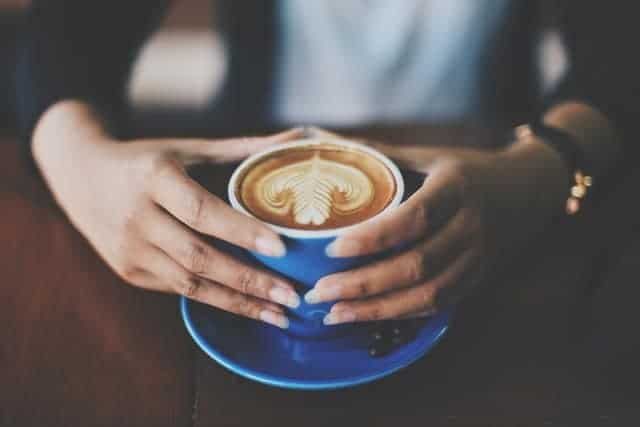 une tasse de café tenue dans vos mains