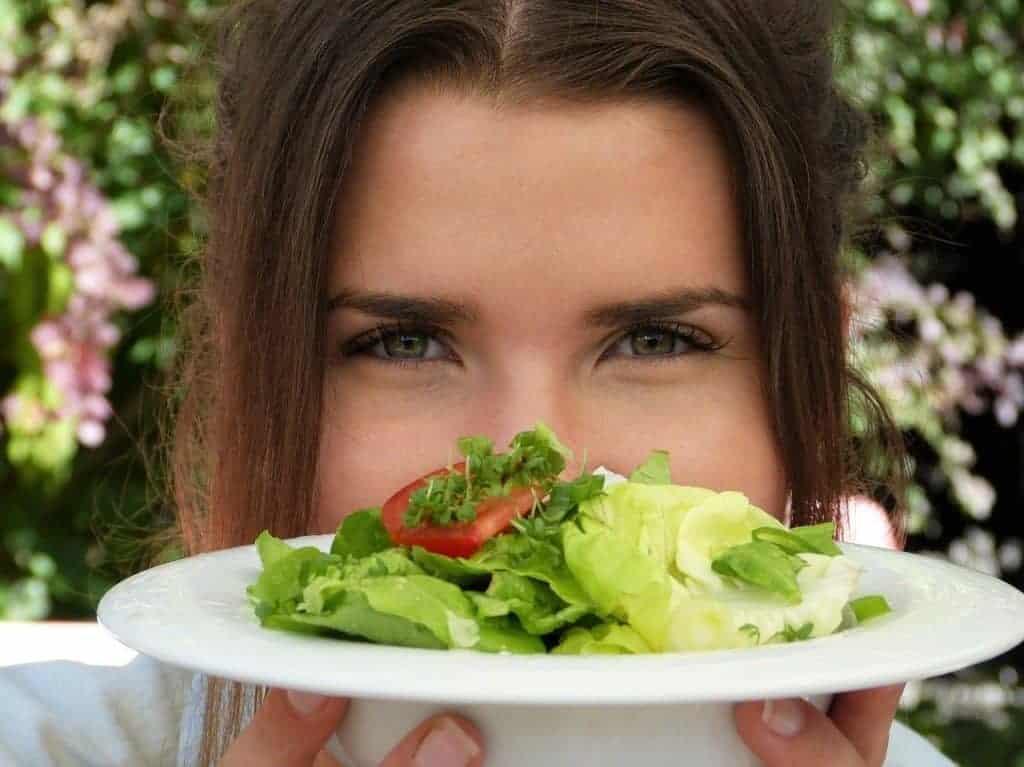 la femme tient une assiette de salade