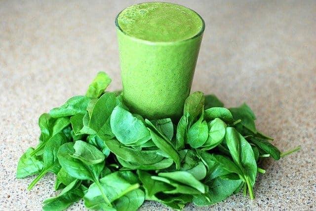 Un verre avec un smoothie vert, des feuilles d'épinards tout autour