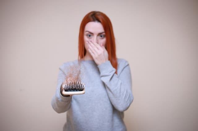 une femme regarde une brosse à cheveux pleine de cheveux