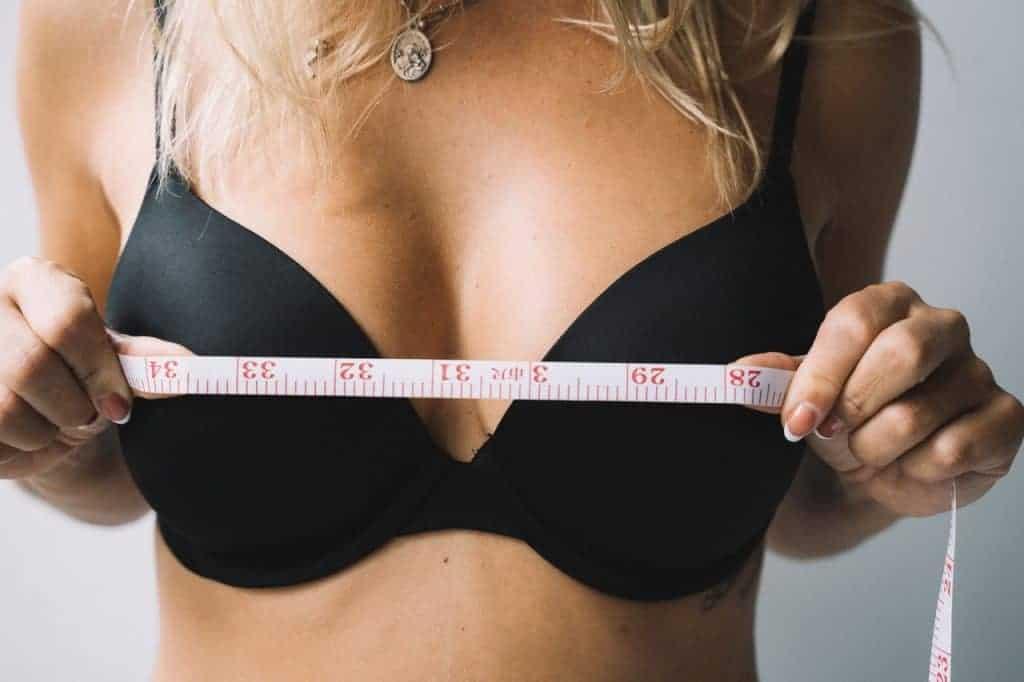 une femme mesure ses seins avec un centimètre