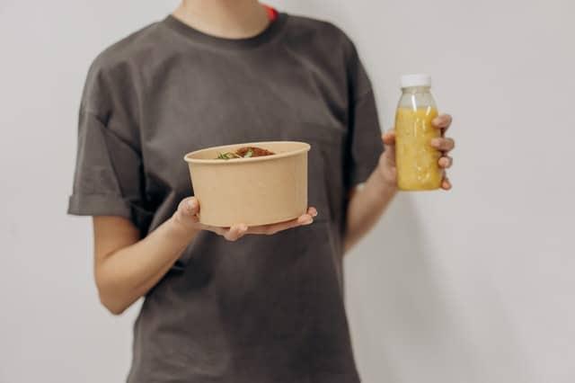 une femme tient un bol de nourriture et un shake