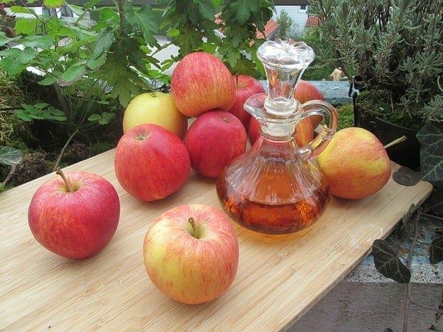 Des pommes fraîches et une bouteille de vinaigre de cidre de pomme sur la table