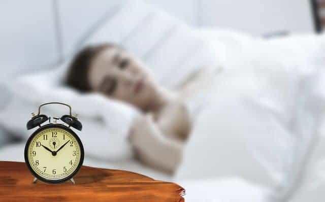 une femme dort avec un réveil à côté de son lit