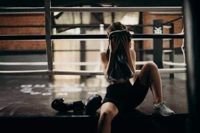 Une femme essuie la sueur de son visage après une séance d'entraînement intense.