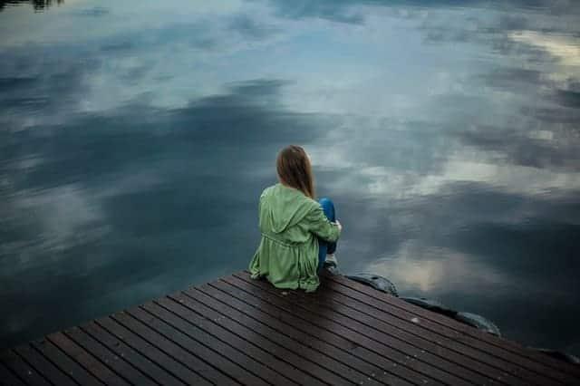 une femme est assise sur le bord d'une jetée et regarde l'eau.
