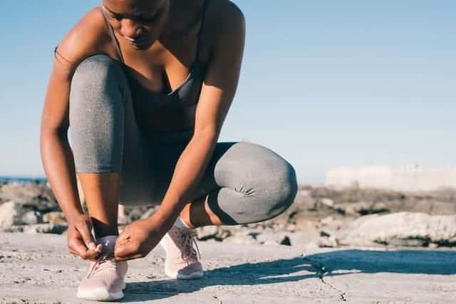 une femme en tenue de sport attache sa chaussure