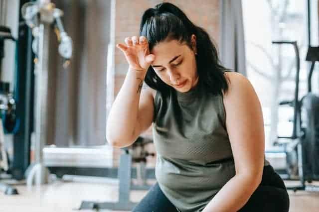 Femme en surpoids fatiguée après une séance d'entraînement