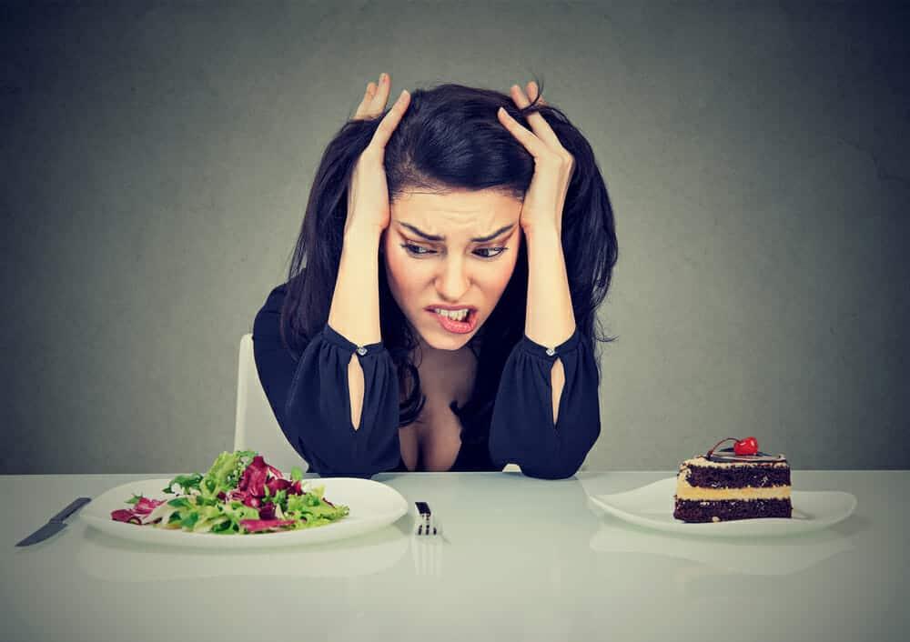 une femme est assise à une table avec une assiette de gâteau et une assiette de salade