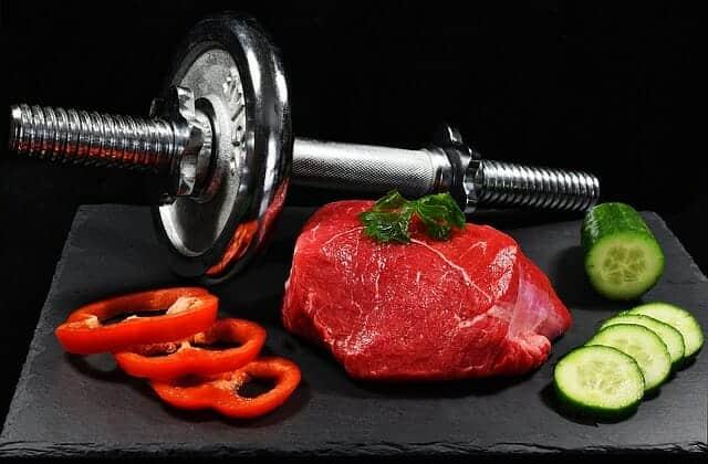 Des haltères, un morceau de viande et des légumes