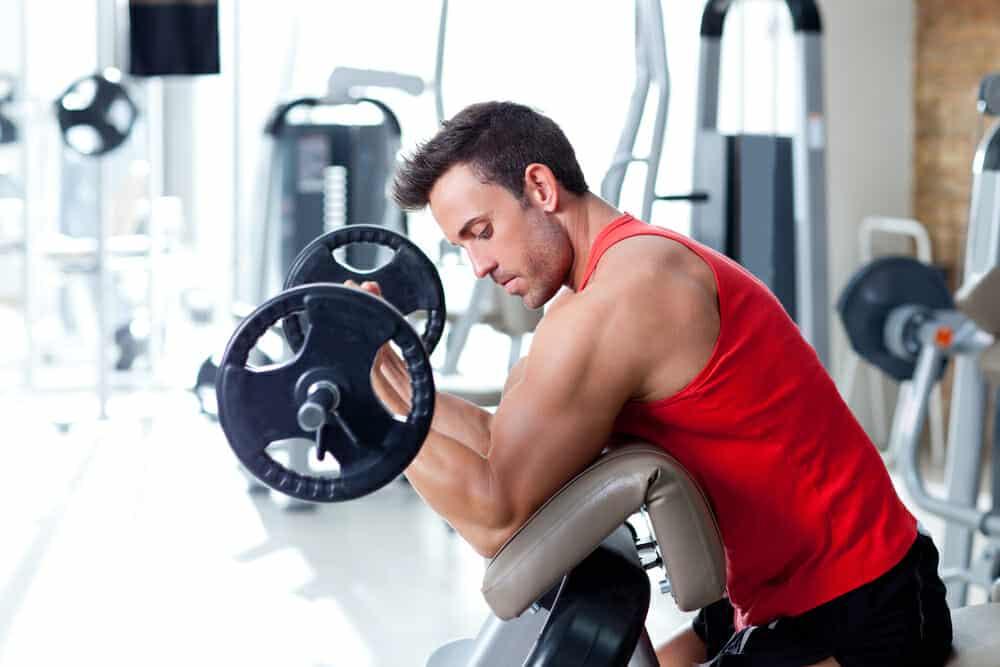 Un homme s'exerce avec une barre d'haltères à la salle de sport.